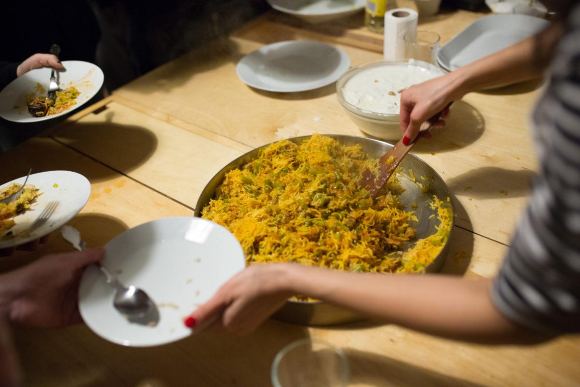 Zwei Hände füllen Reis und Gemüse auf einen Teller.