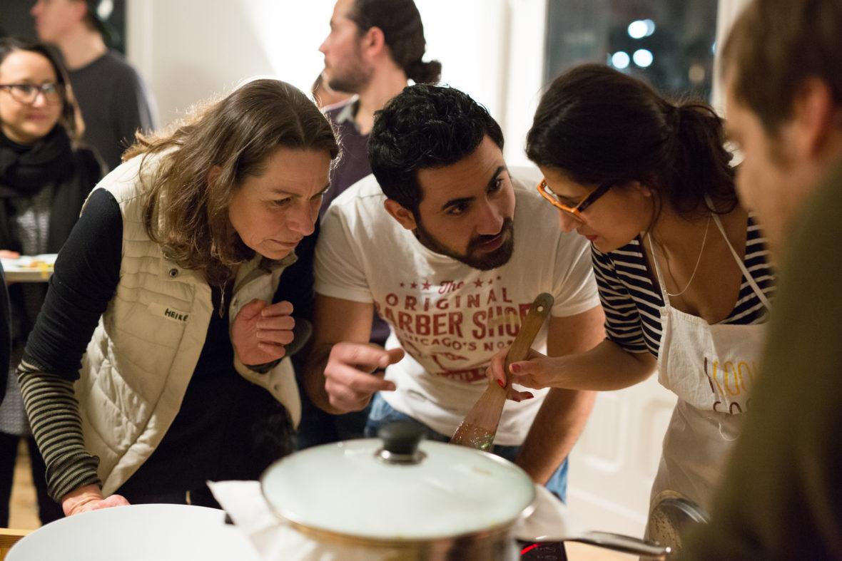 Mehrere Teilnehmer beugen sich gestikulierend über einem Topf