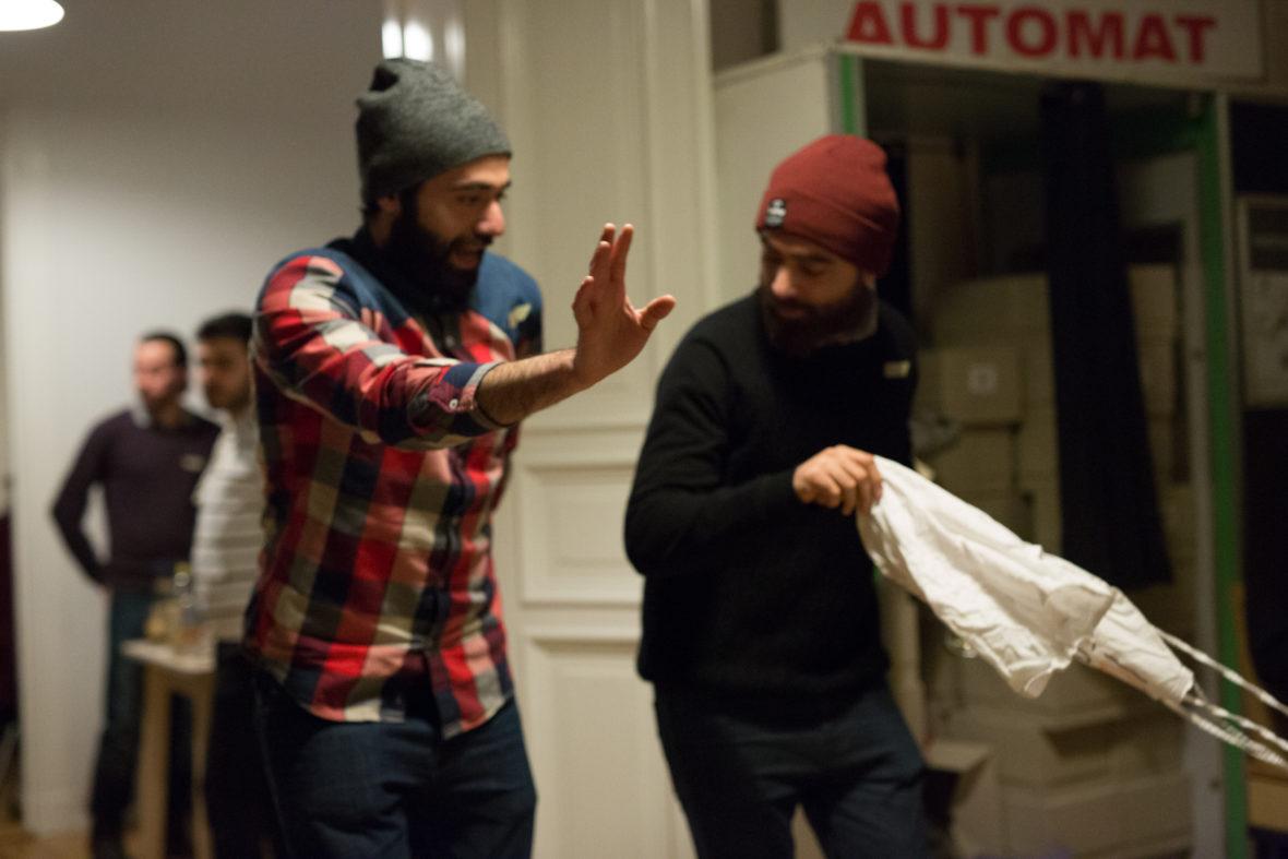 Zwei Männer tanzen, einer wirbelt eine Schürze umher.