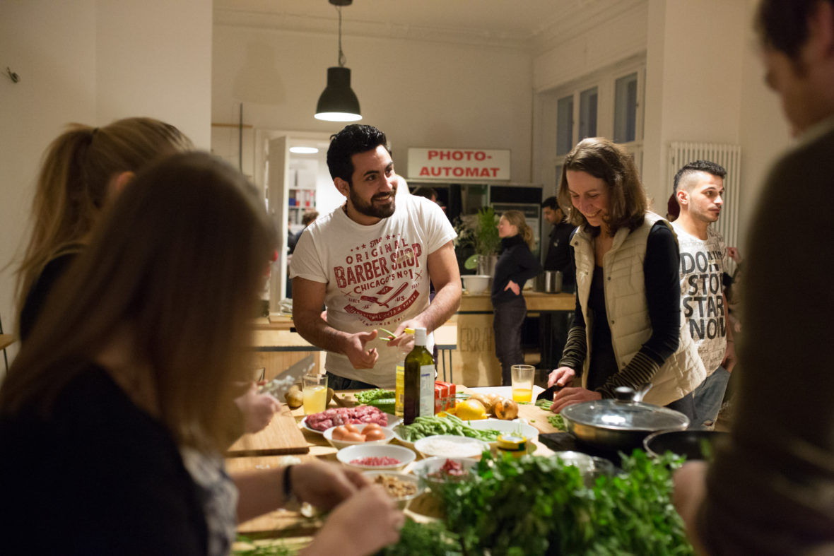 Ein Mann und eine Frau stehen an einem Tisch voller Zutaten und kochen.