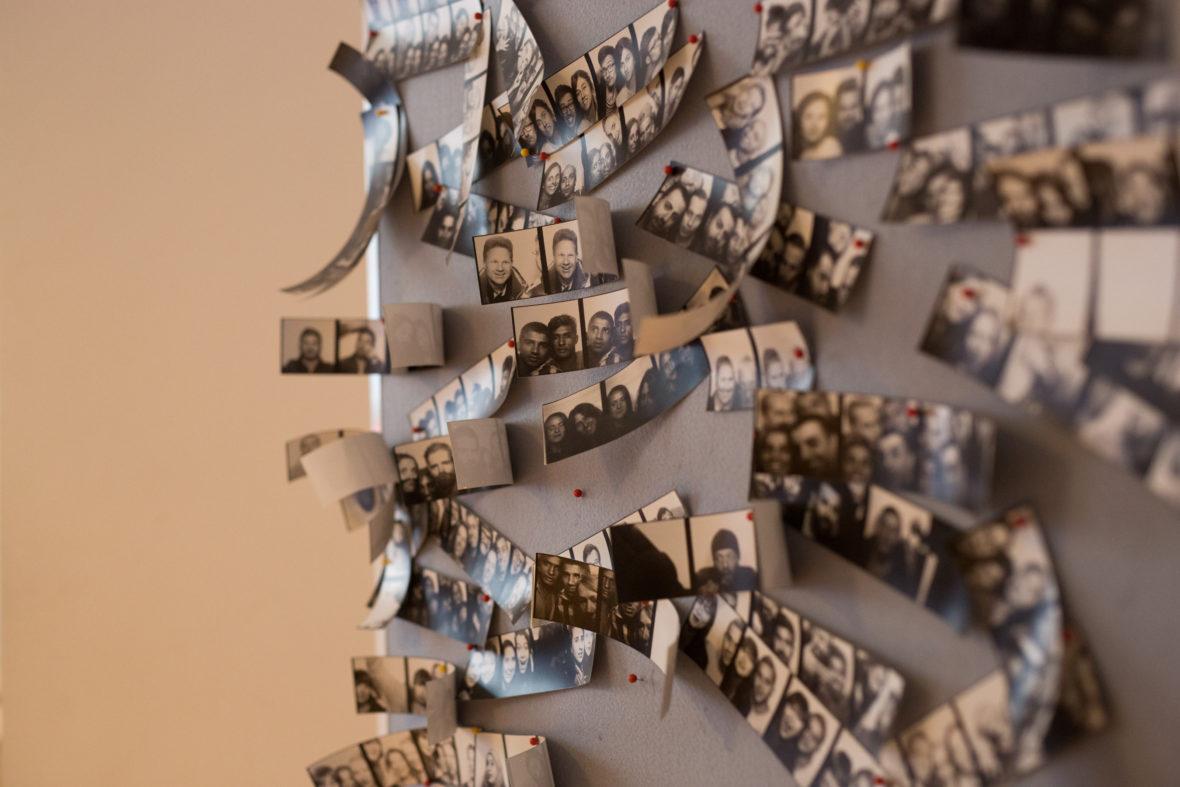 An einer Pinnwand hängen viele Bilder aus Foto-Automaten.