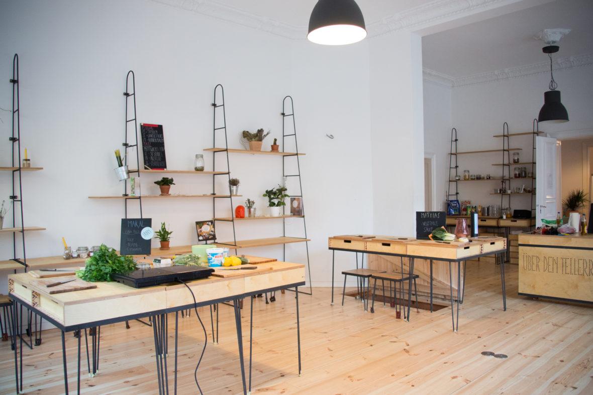 Blick in einen Raum voller Tische, auf denen Kochzutaten liegen.