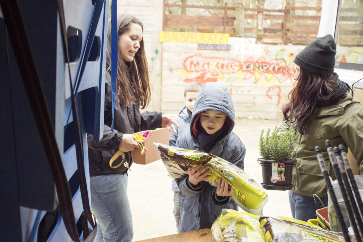 Ein anderes Mädchen trägt eine Packung Blumenerde aus dem dem Sportmobil.