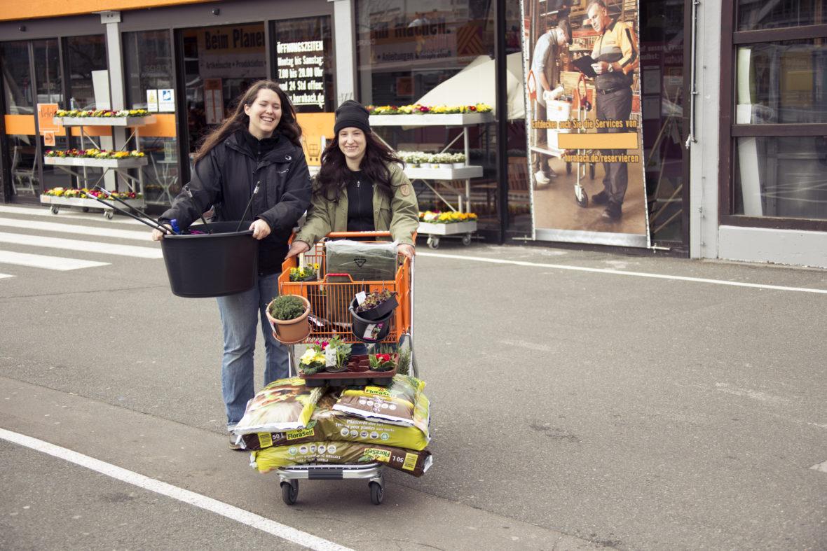 Katharina Kildau und Lena Schmitt schieben einen Einkaufswagen voller Blumen und Blumendere über einen Parkplatz.