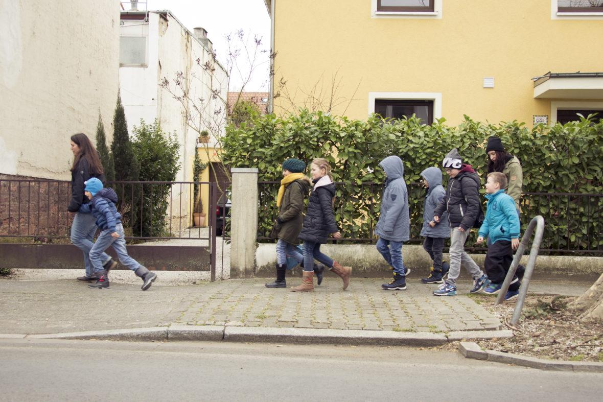 Zwei Frauen und viele Kinder gehen eine Straße entlang.