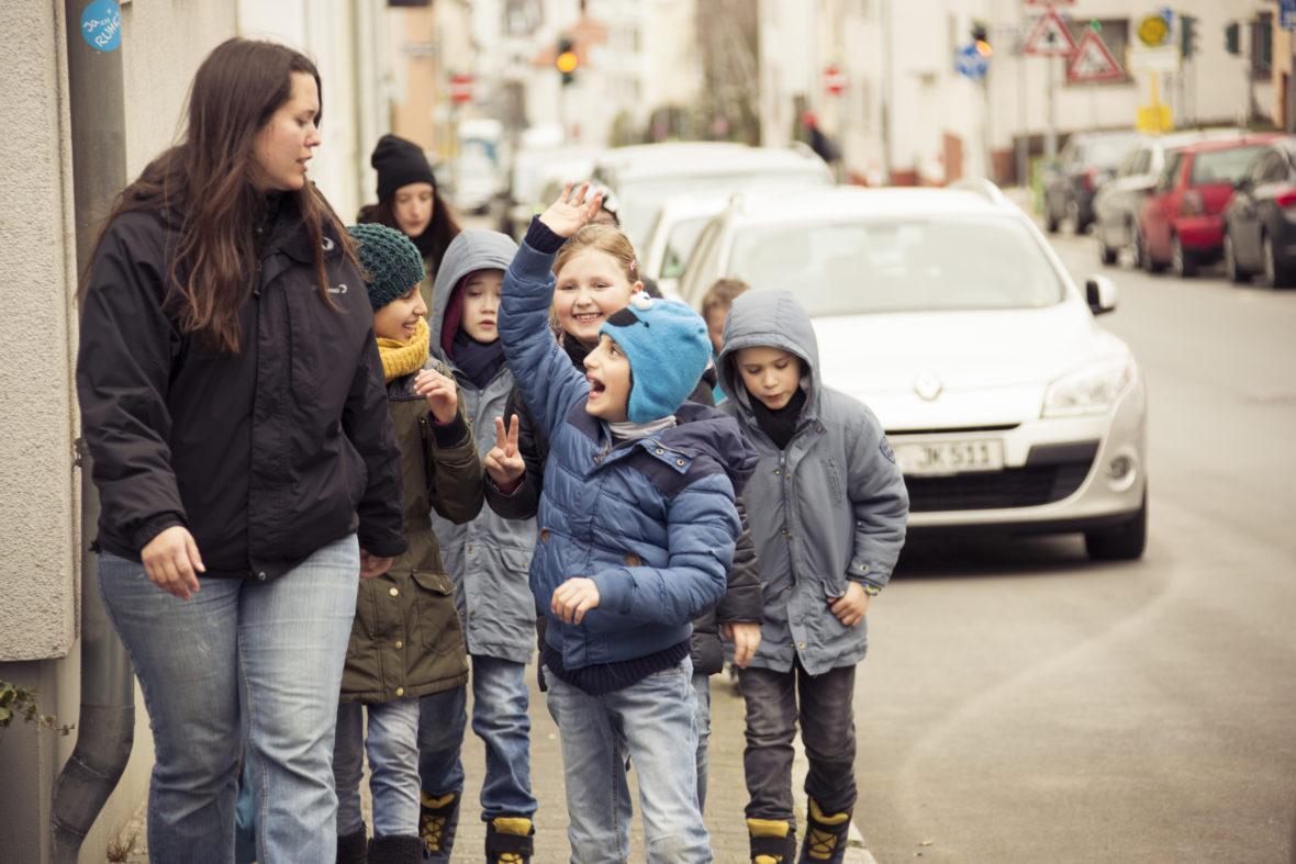 Eine Frau und viele Kinder gehen eine Straße entland.