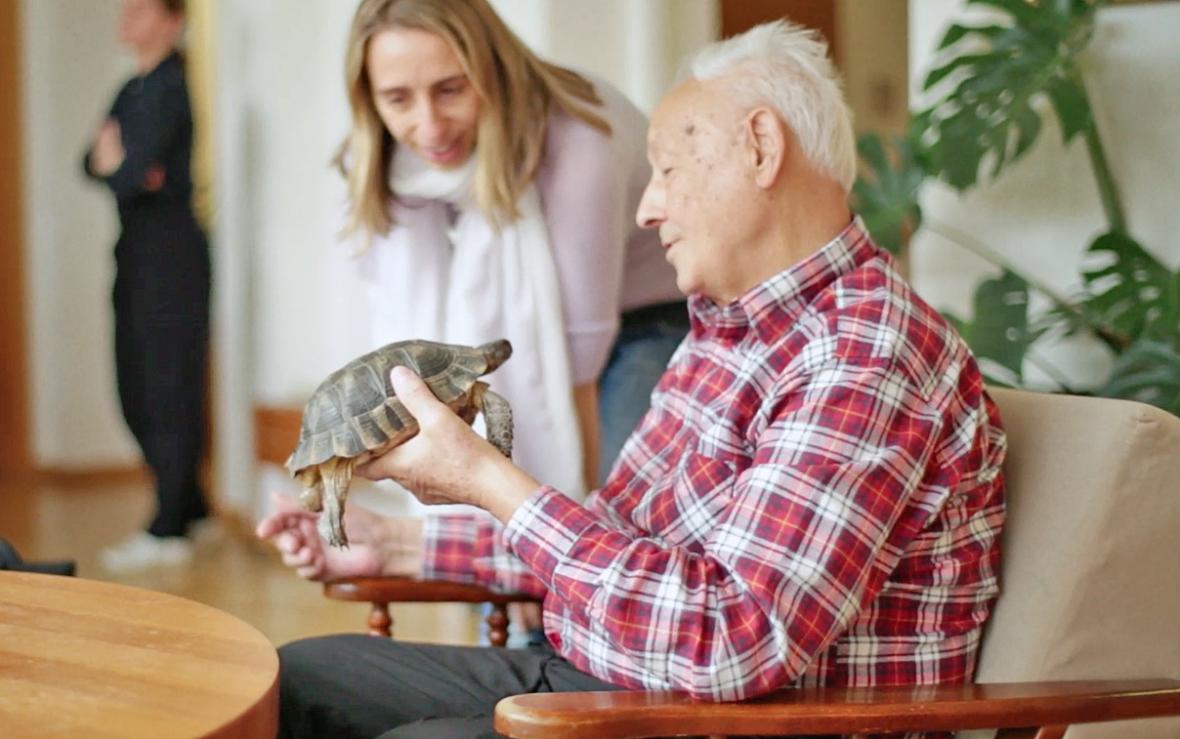 Ein alter Mann hält eine Schildkröte in der Hand.