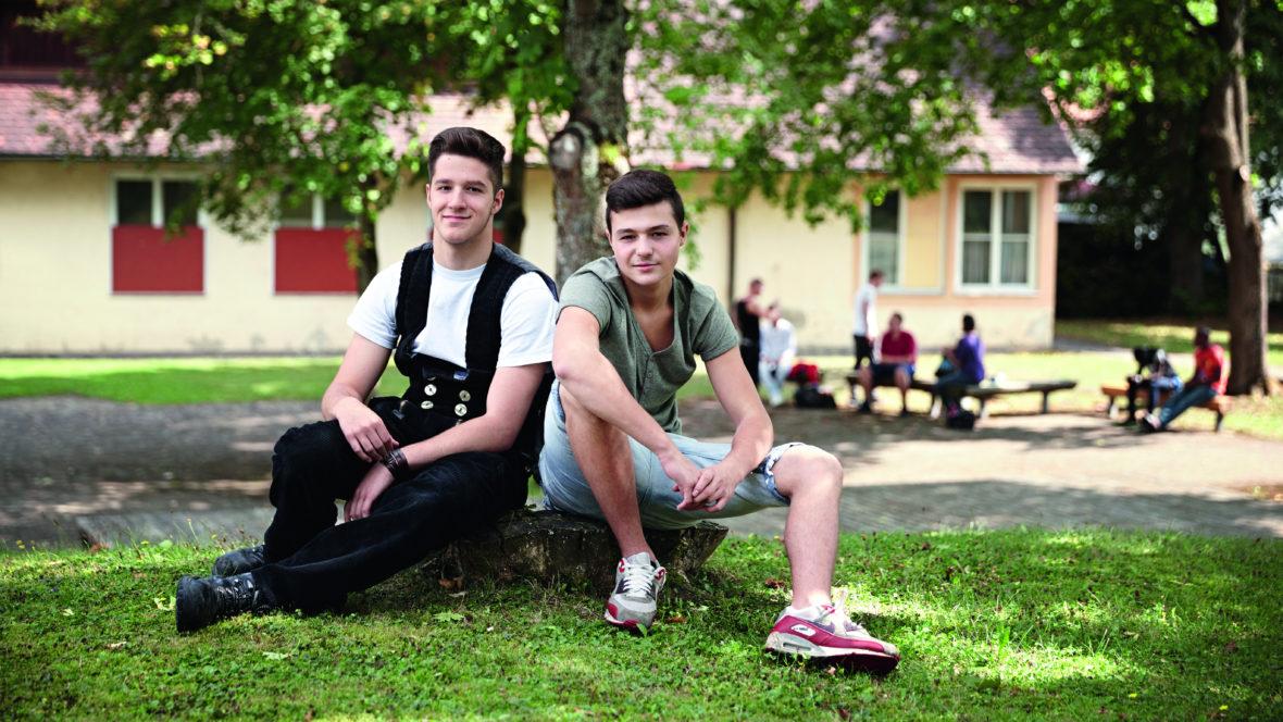 Zwei junge Männer, der linke in Zimmermannskleidung, sitzen vor einem Baum.
