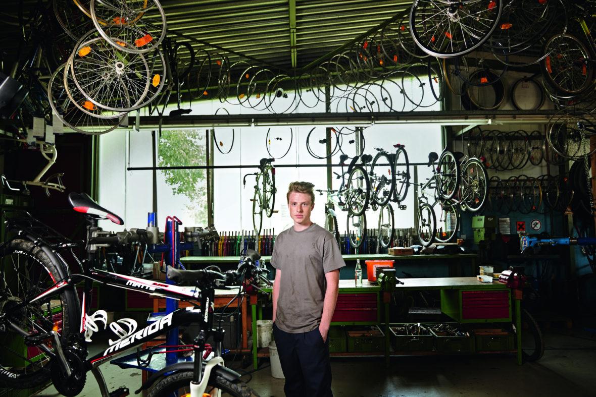 Ein junger Mann steht, die Hände in den Taschen, in einer Werkstatt, voller Fahrrad-Räder.
