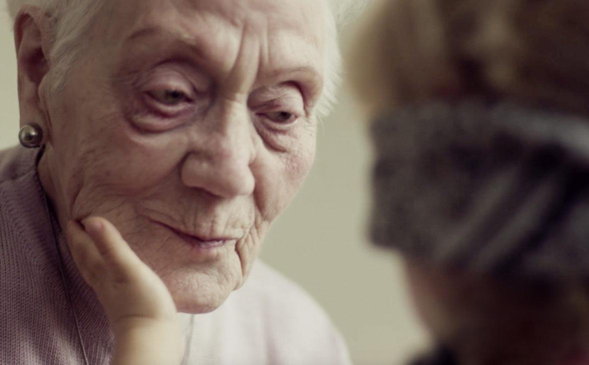 Eine Kinderhand streichelt das Gesicht einer alten Frau.