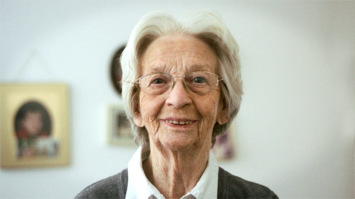 Eine Frau mit Brille und weißem Haar schaut lächelnd in die Kamera