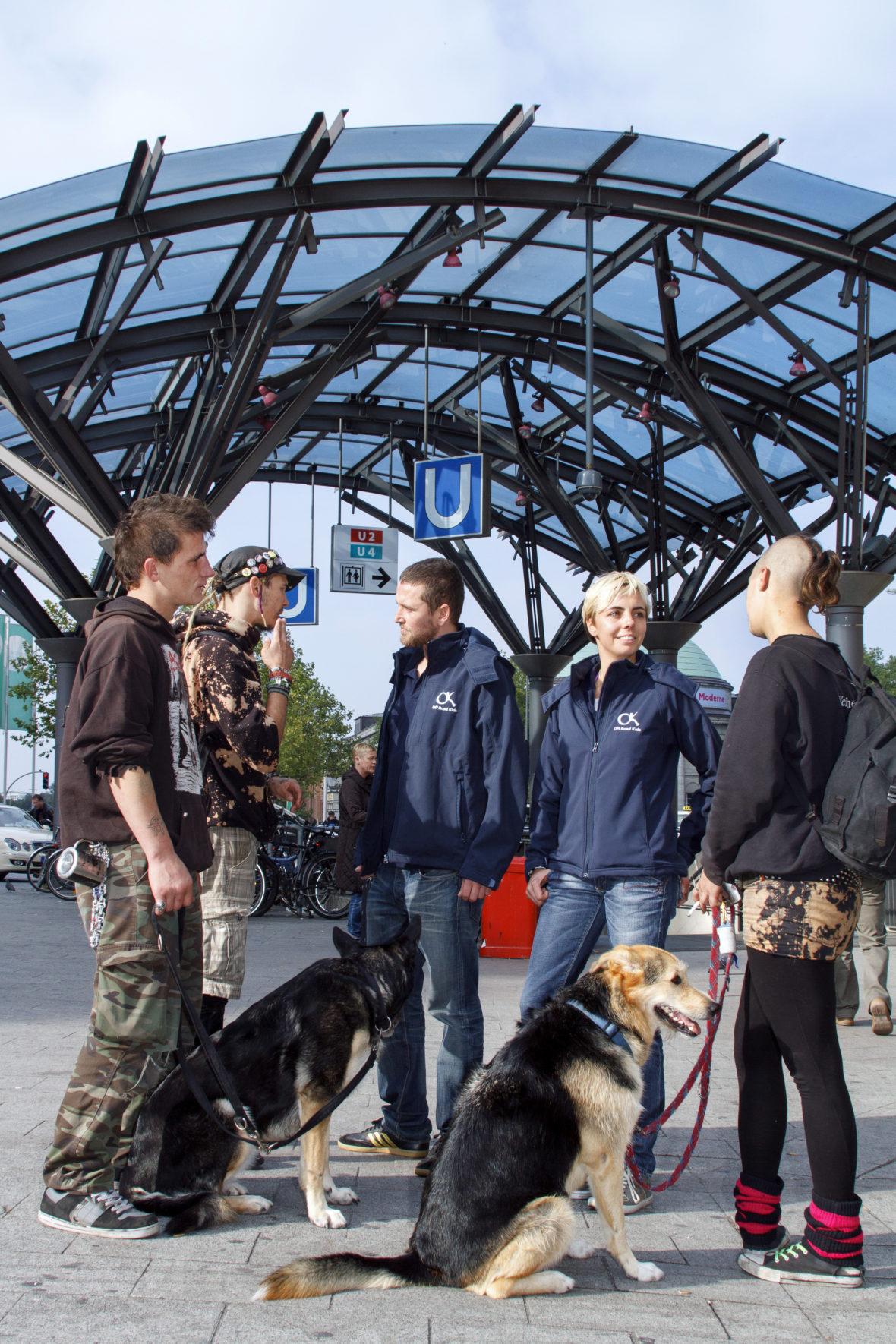 Zwei Sozialarbeiter stehen mit drei Jugendlichen und ihren Hunden am Bahnhof und unterhalten sich.