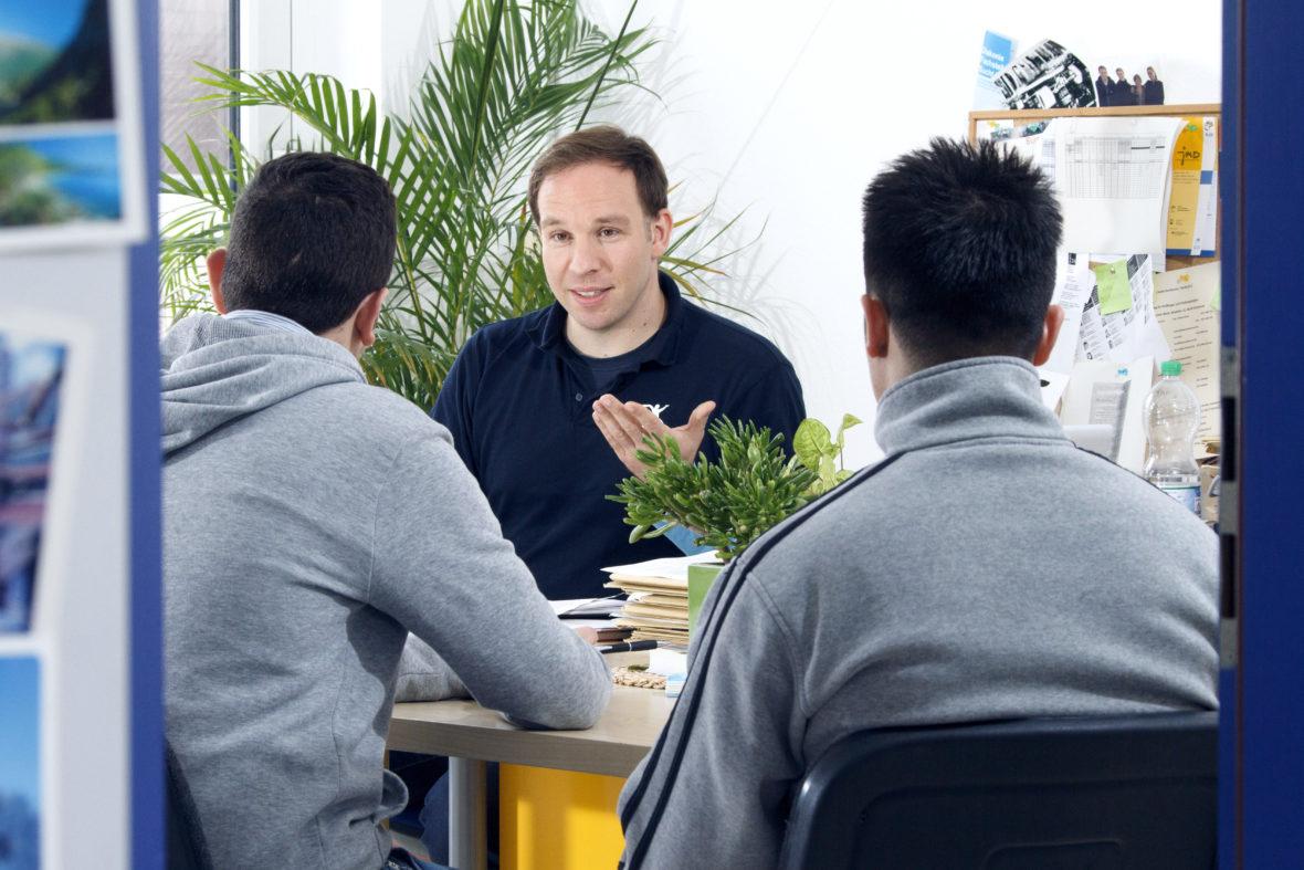 Ein Sozialarbeiter sitzt zwei jungen Männern gegenüber am Schreibtisch und spricht.