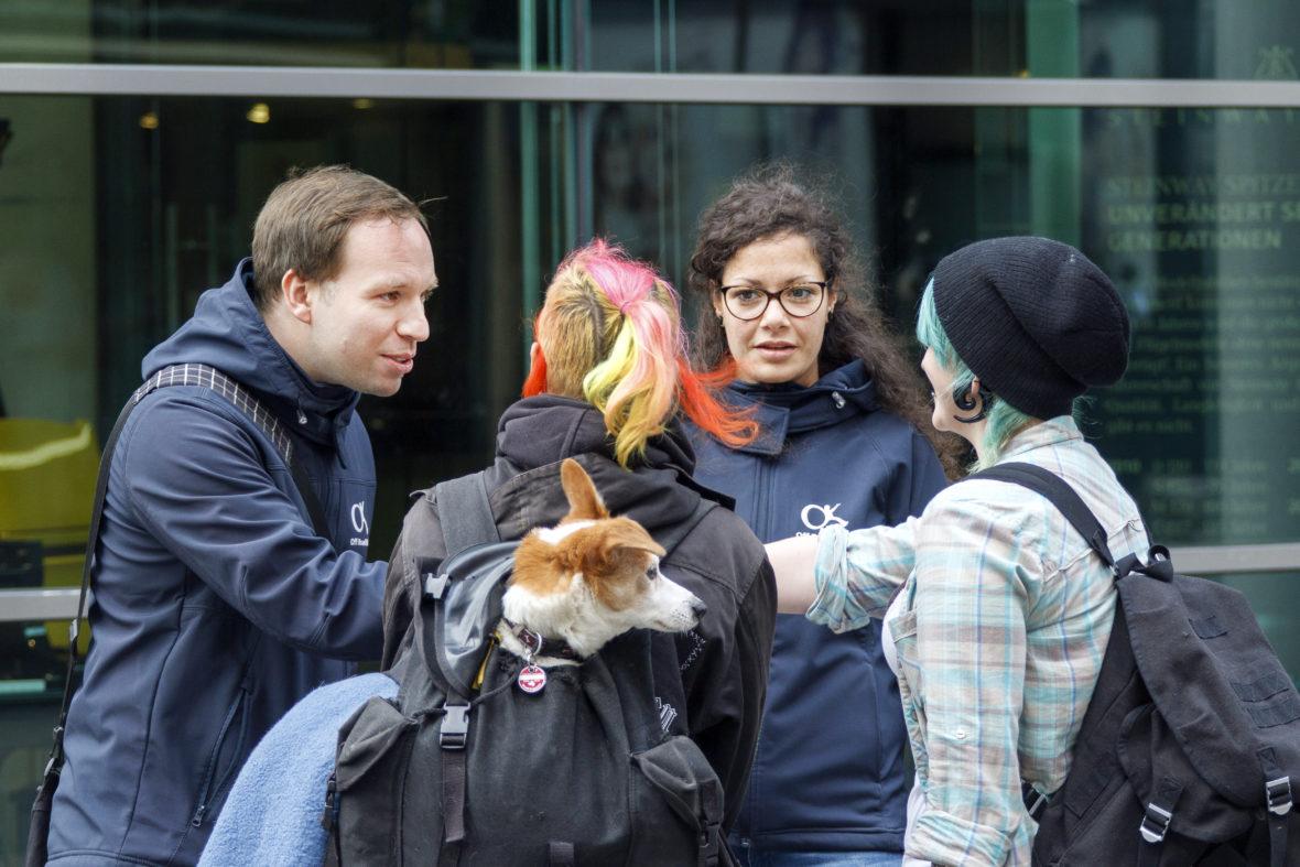 Zwei Sozialarbeiter und zwei Mädchen mit bunten Haaren reden miteinander.