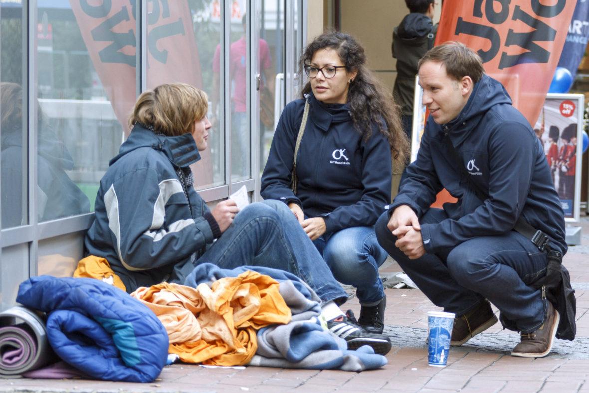 Zwei Sozialarbeiter und ein Mädchen, das an einer Wand hockt und von Decken umgeben ist, reden miteinander.