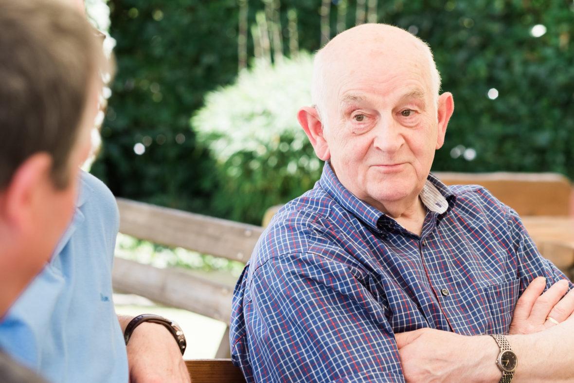 Ein alter Mann im Karohemd hört einem anderen Mann zu und verschränkt die Arme.