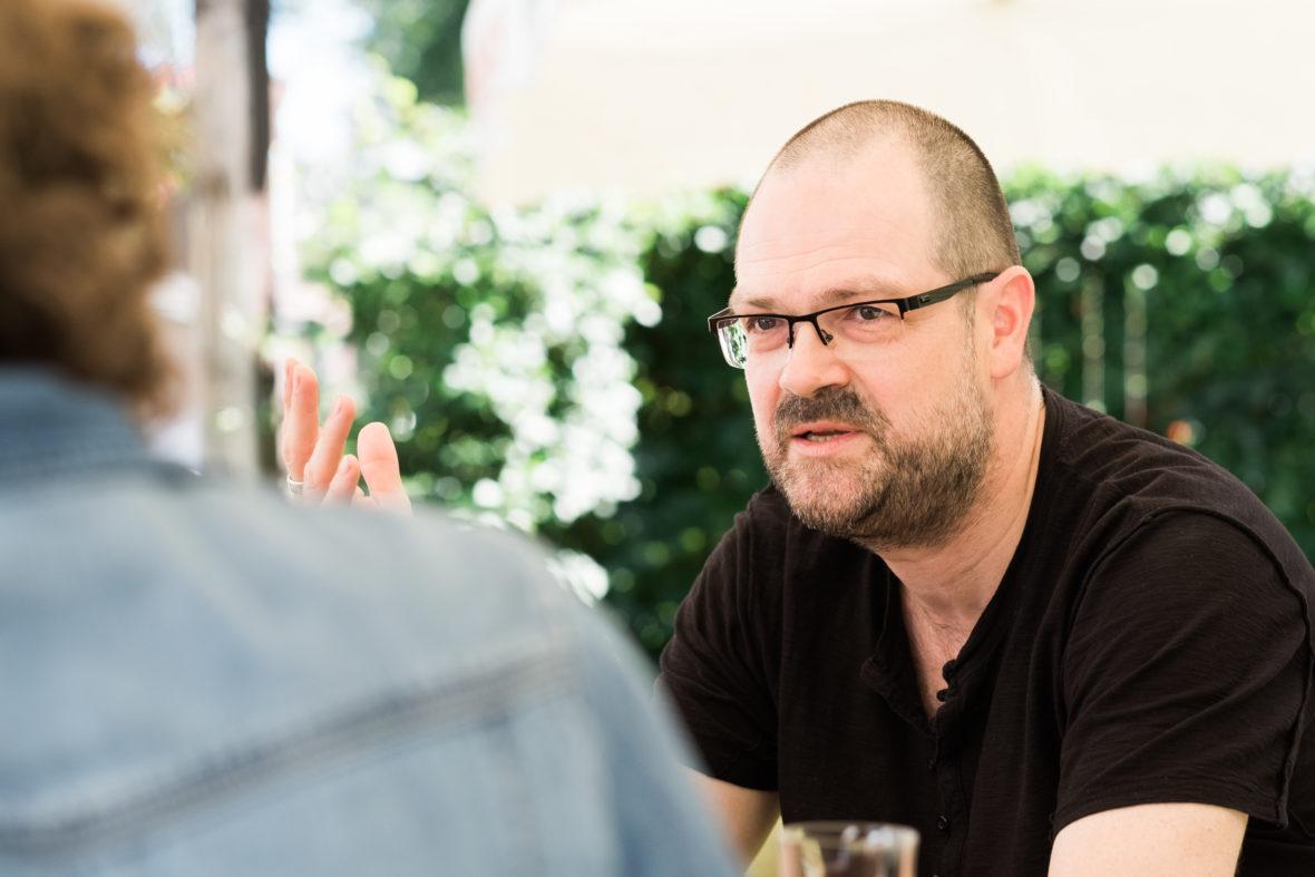 Ein Mann mittleren Alters mit einer Brille gestikuliert beim Sprechen.