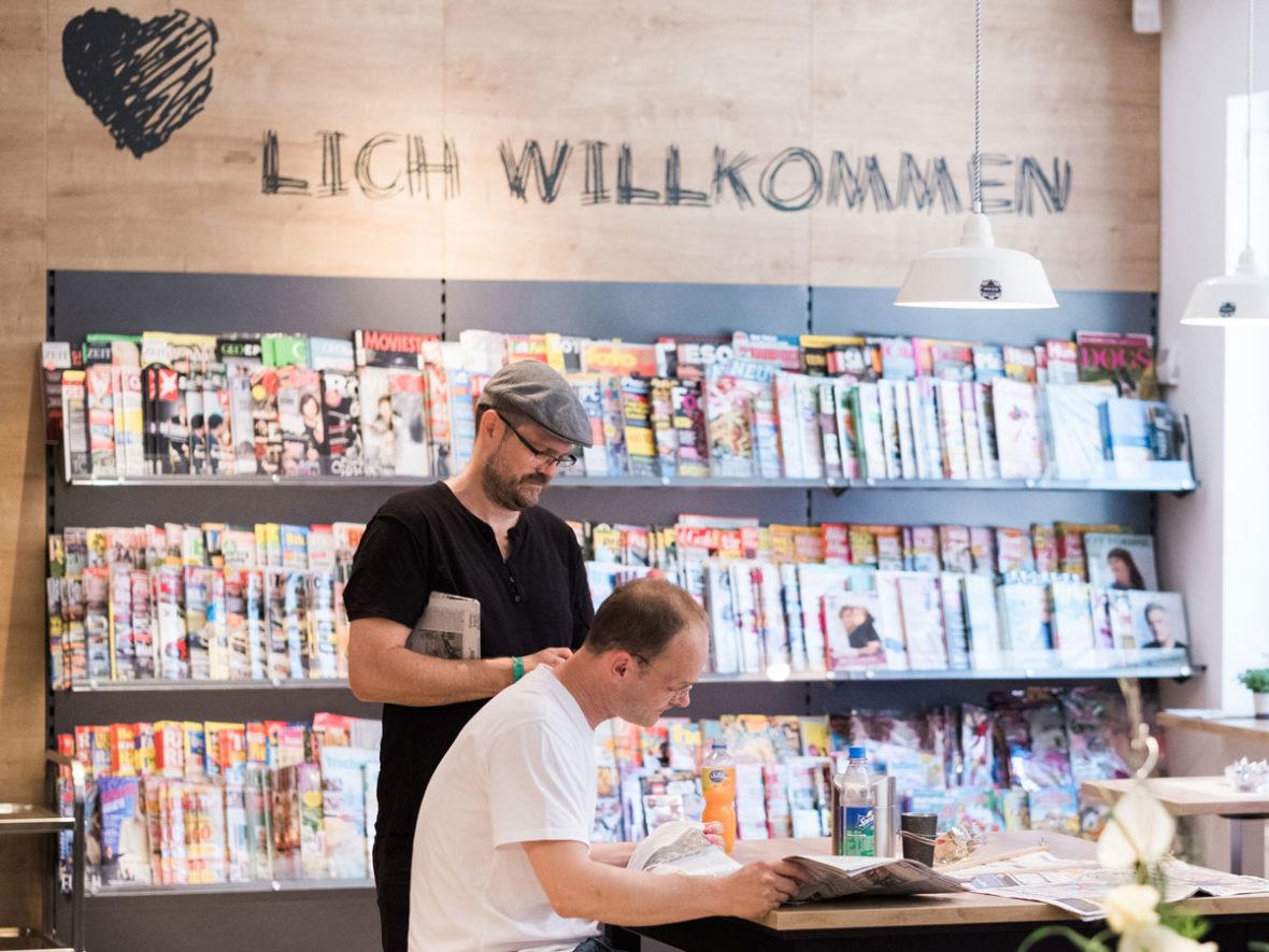 Ein Mann mit einer Baskenmütze steht vor einem Zeitschriftenregal und liest, ein anderer sitzt an einem Tisch und schaut in die Zeitung.