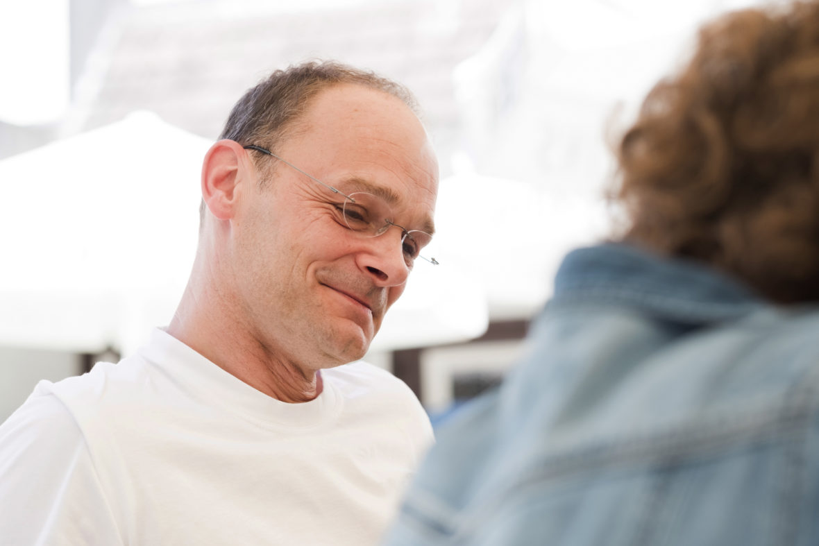 Ein Mann mit randloser Brille und weißem T-Shirt blickt lächelnd nach unten.