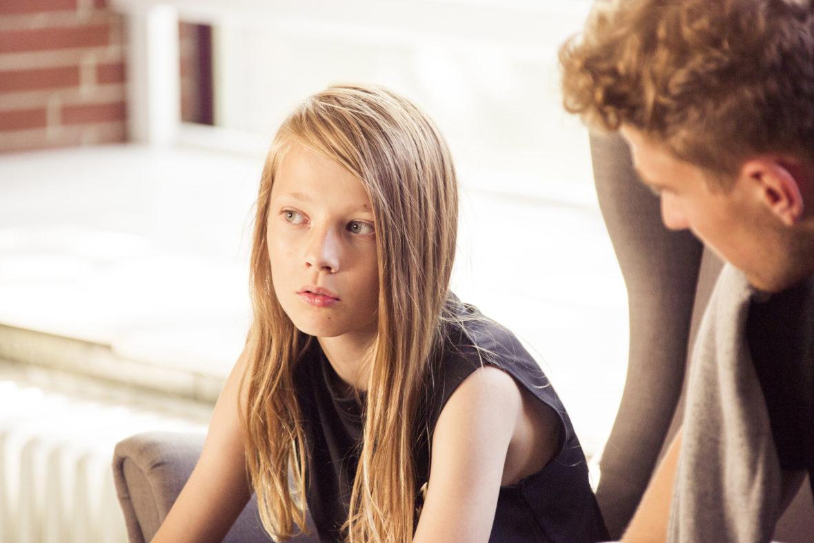 Ein Junge und ein junger Erwachsener sitzen zusammen, der Junge denkt nach.