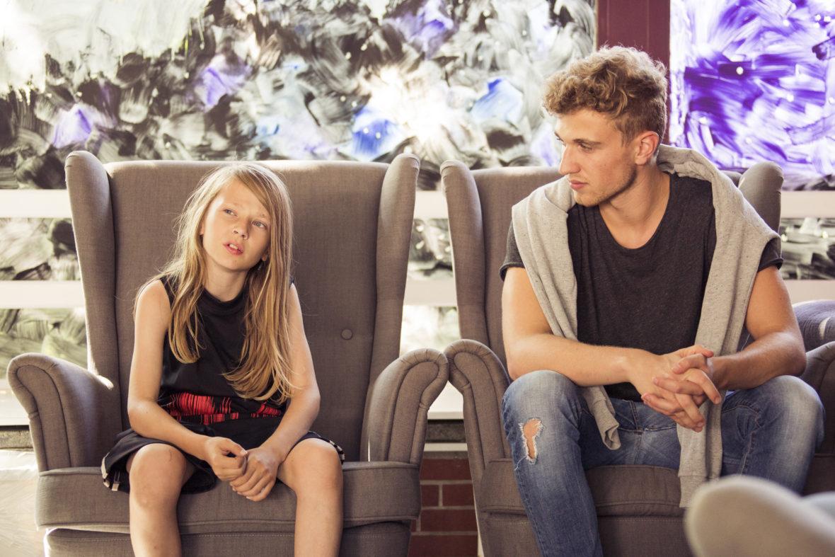Ein junge mit langen Haaren und ein junger Erwachsener sitzen nebeneinander auf grauen Ohrensesseln, der Junge erzählt, der andere hört aufmerksam zu.