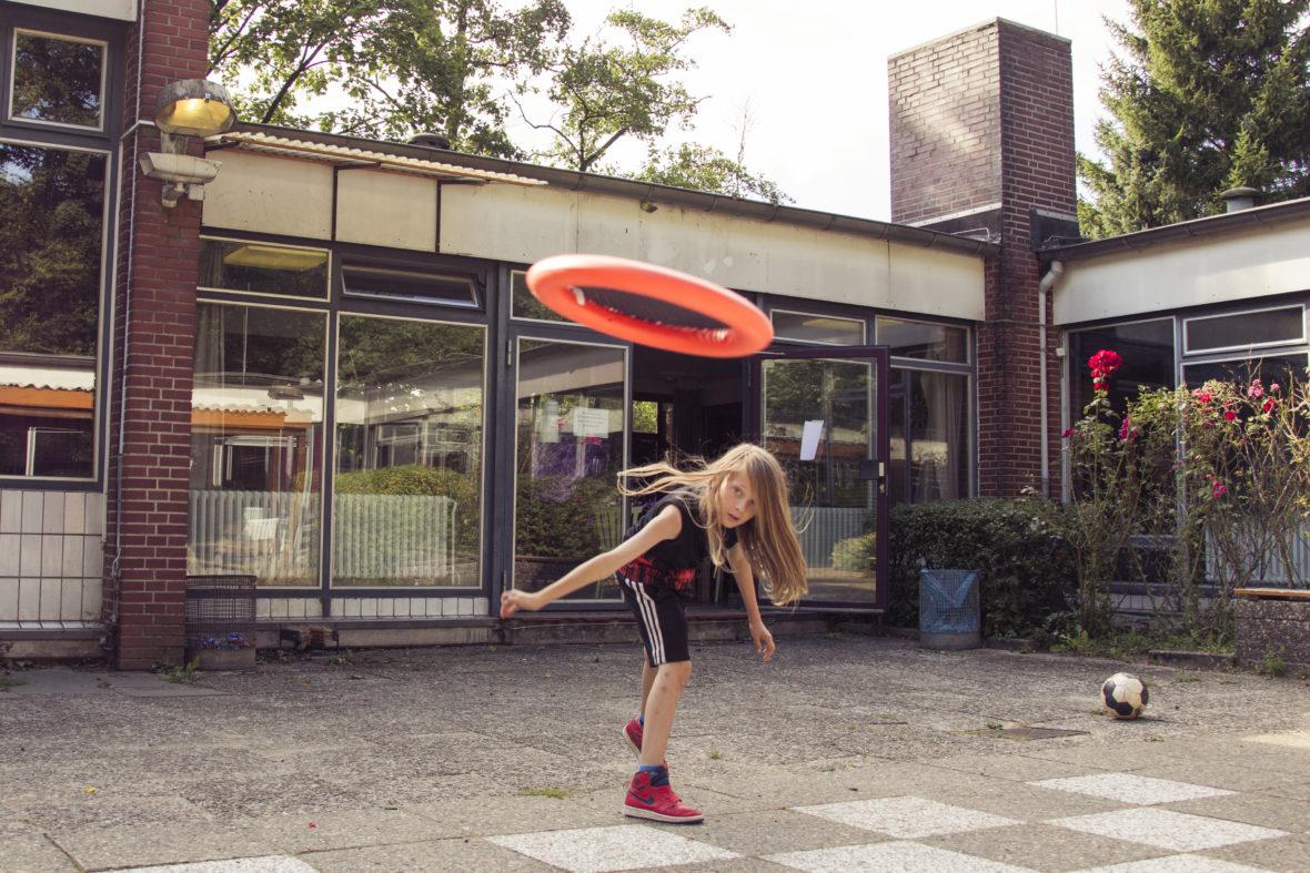 Ein Junge mit langen Haaren wirft ein Frisbee.