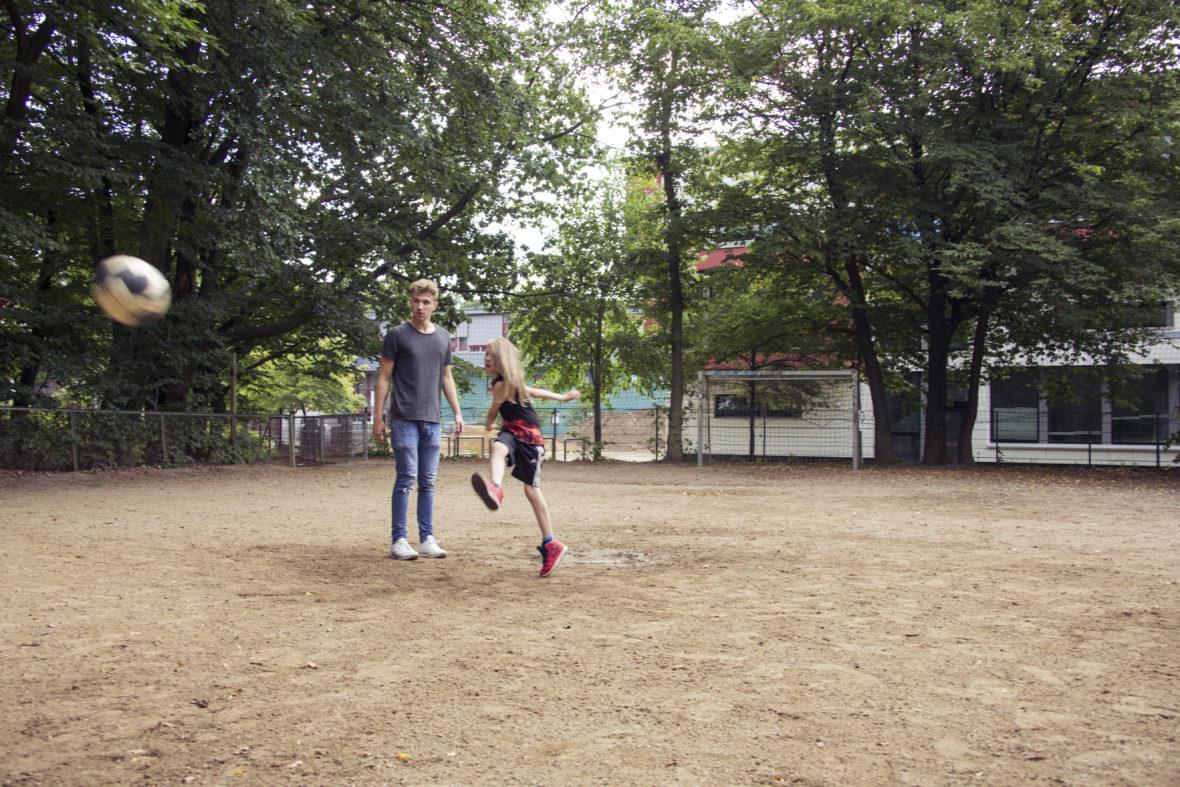 Ein Junge mit langen Haaren tritt hart einen Fußball, ein junger Erwachsener schaut ihm zu.