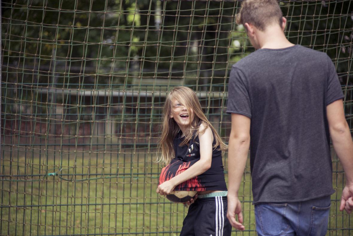 Ein Junge mit langen Haaren versteckt einen Fußball unter seinem T-Shirt und lacht. Ein Erwachsener will ihm neckisch den Ball abnehmen.