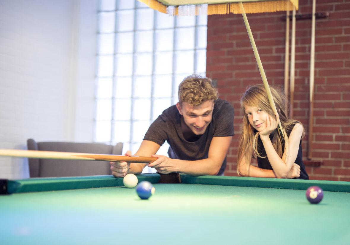 Ein junger Mann und ein Junge stehen an einen Billiard-Tisch gelehnt.