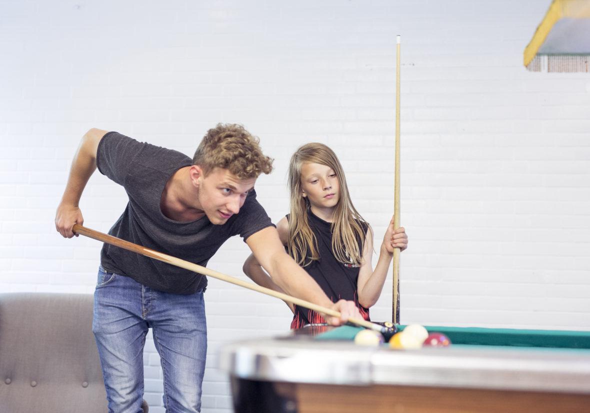 Ein junger Mann mit Locken stößt eine Billiardkugel an, ein Junge mit langem Haar hält seinen Queue und schaut ihm dabei zu.