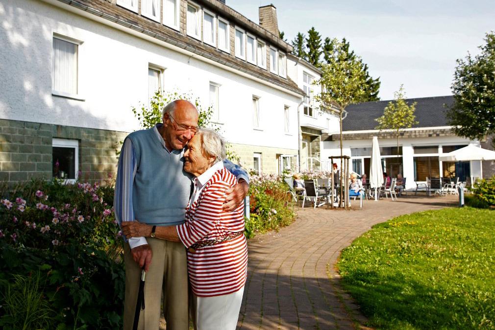 Ein alter Mann und eine alte Frau umarmen sich innig im Hof eines Pflegeheims.