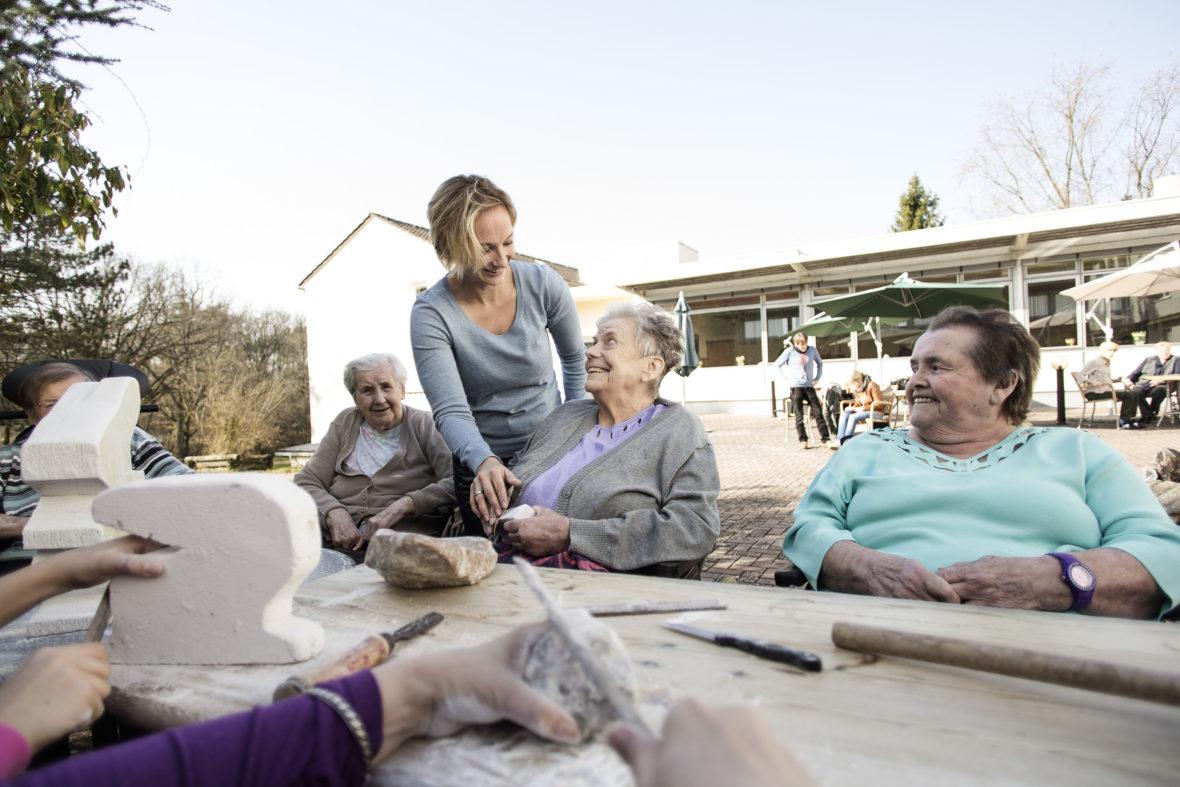 Eine Betreuerin lacht mit mehren alten Damen, die an einem Tisch im Freien Figuren aus Ytong schnitzen.