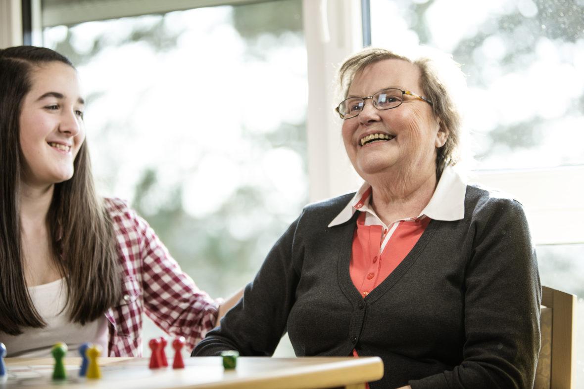 Eine junge Frau streicht einer älteren Dame über den Arm, beide lächeln.