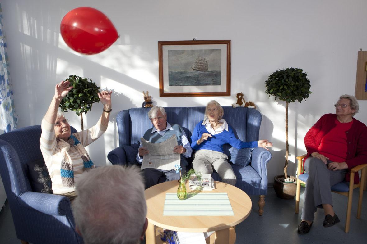 Ältere Bewohner eines Pflegeheims spielen mit einem roten Luftballon.