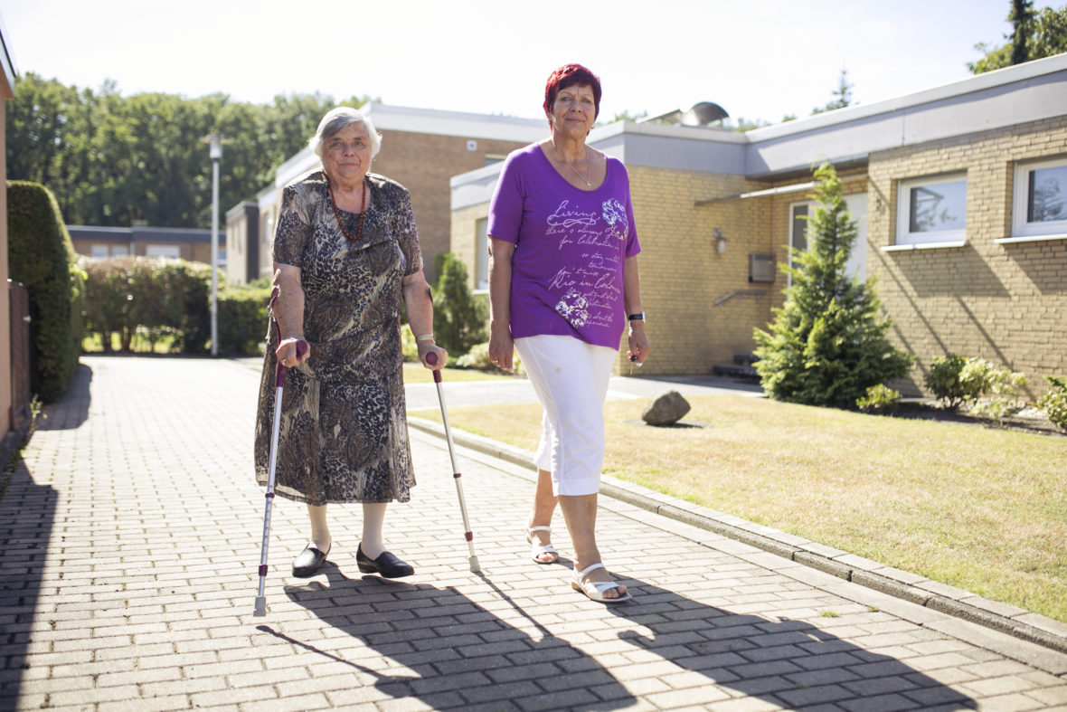 Eine etwas jüngere Frau und eine ältere Dame mit Krücken gehen gemeinsam über die Straße.