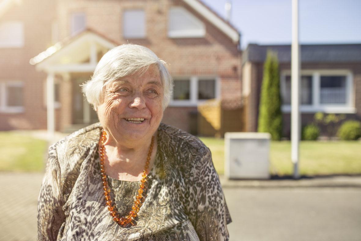 Eine ältere Dame mit oranger Perlenkette und grauem Haar lächelt.