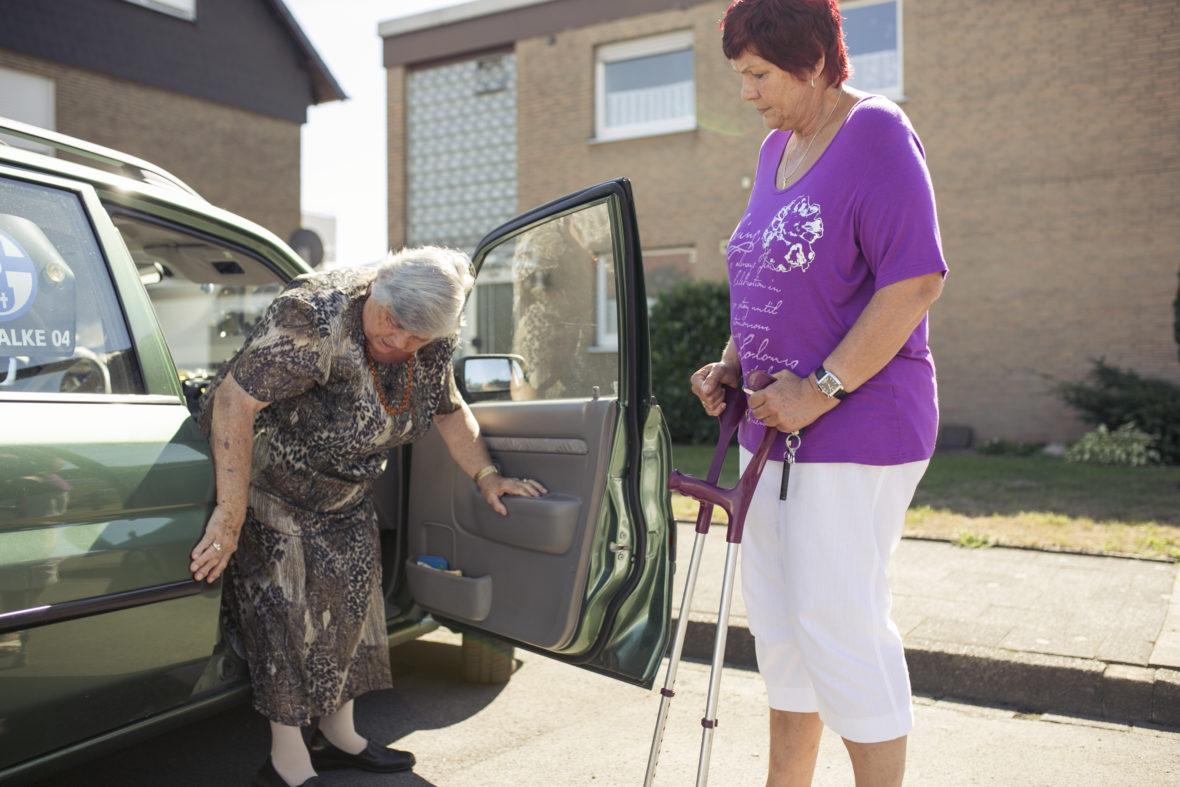 Eine etwas jüngere Frau wartet mit Krücken, bis eine ältere Dame aus dem Auto ausgestiegen ist.