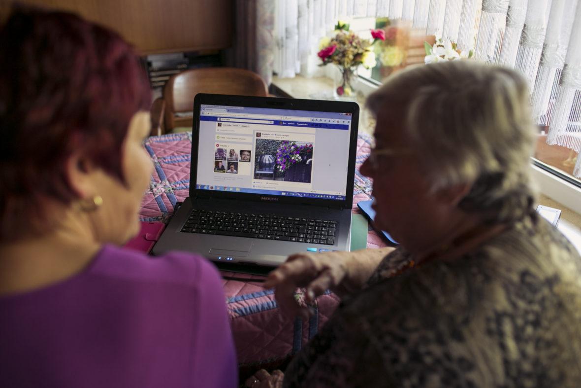 Eine etwas jüngere und eine alte Frau sehen sich eine Seite auf der Plattform Facebook an.