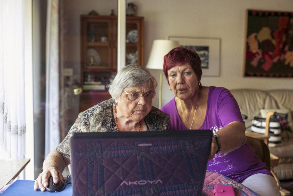 Eine ältere Dame sitzt mit ihrer etwas jüngeren Freundin am Laptop, die Freundin zeigt ihr etwas auf dem Bildschirm.