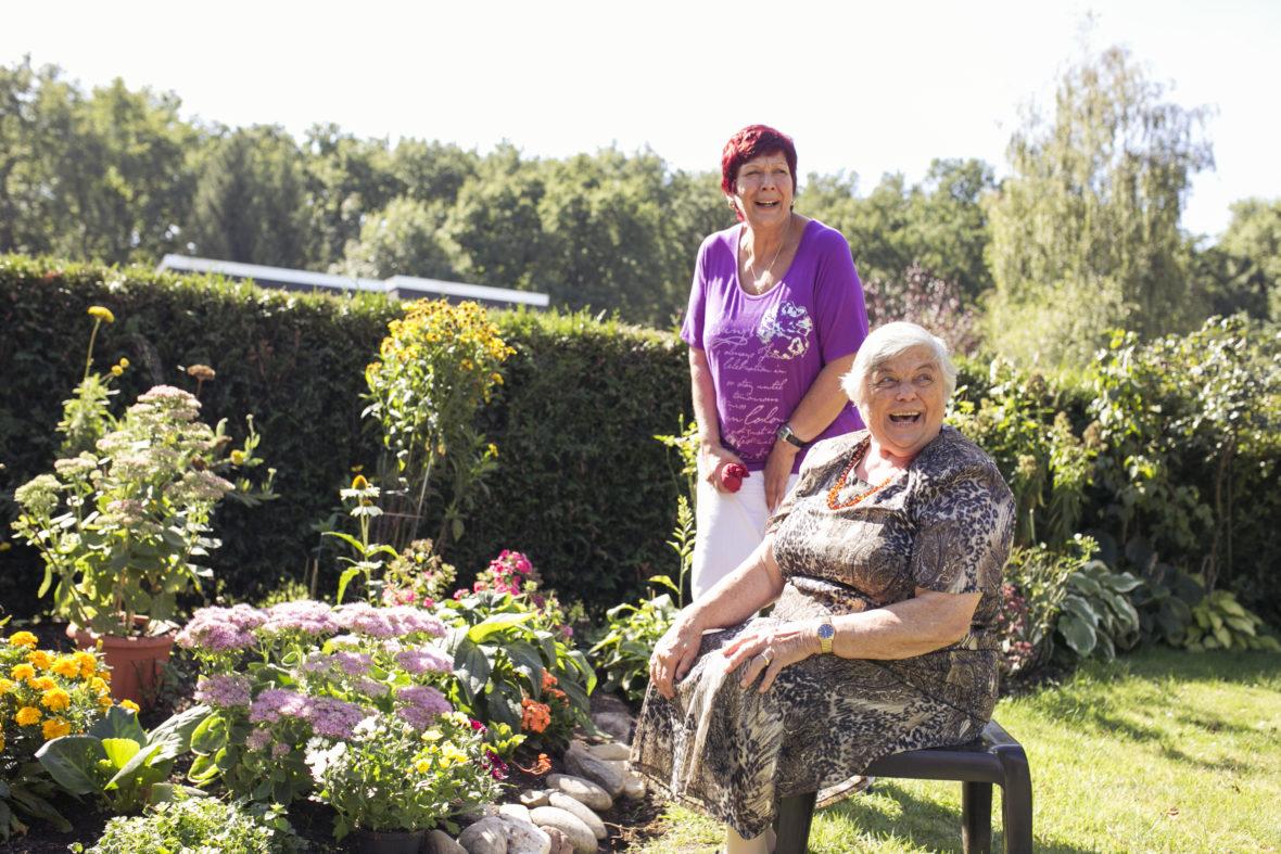 Zwei Frauen, eine ältere auf dem Stuhl und eine mit roten Haaren sind im Garten und lachen von Herzen.