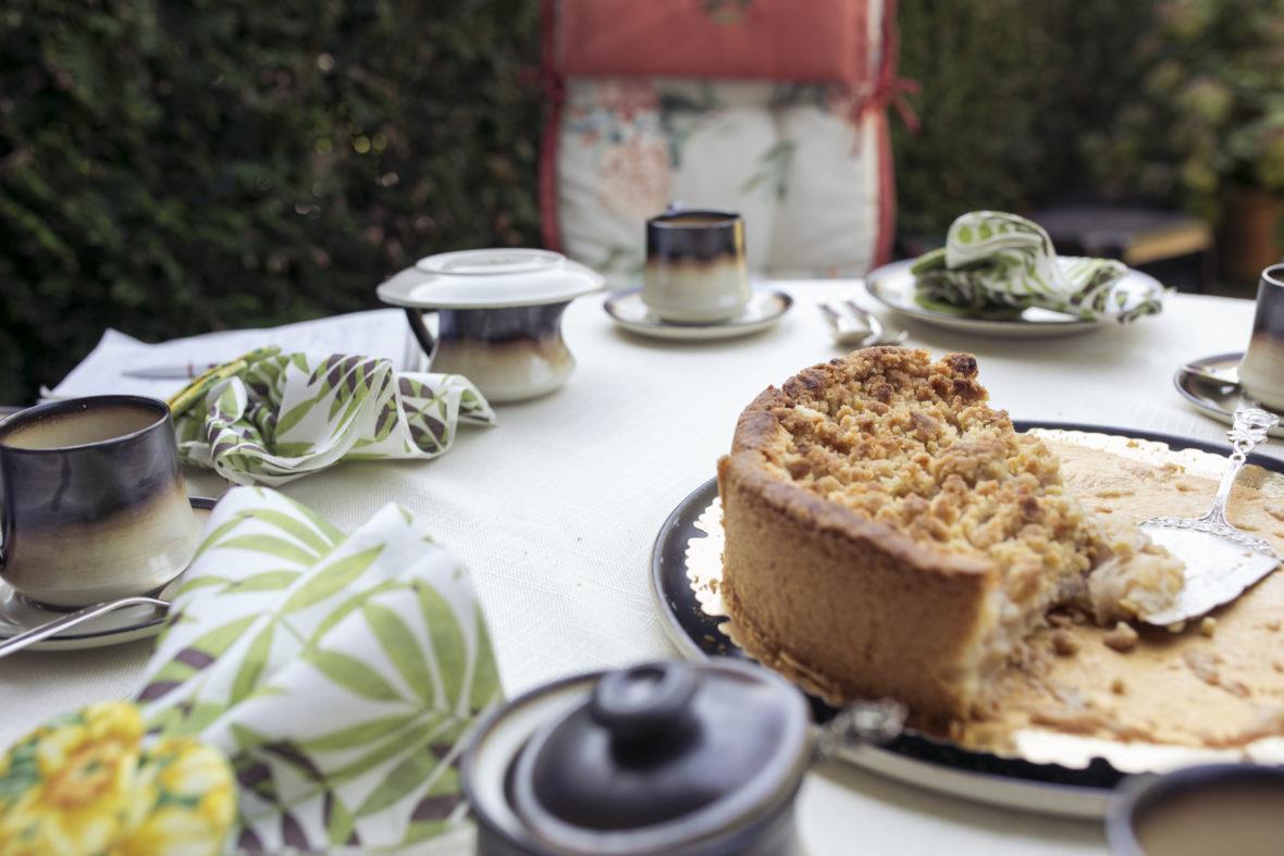 Ein Apfelkuchen steht angeschnitten auf einer schön gedeckten Kaffeetafel.