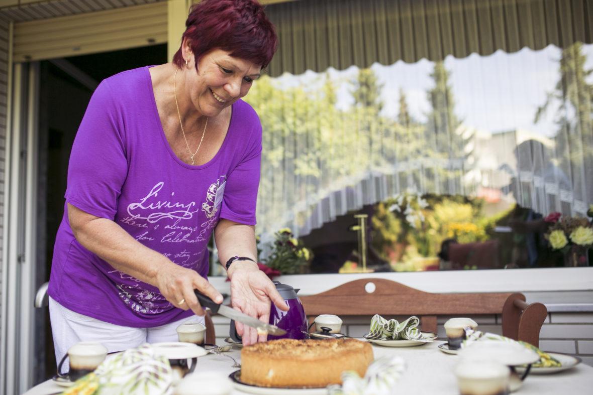 Eine Frau mit roten Haaren und lilafarbenem Sweater schneidet einen Kuchen an.