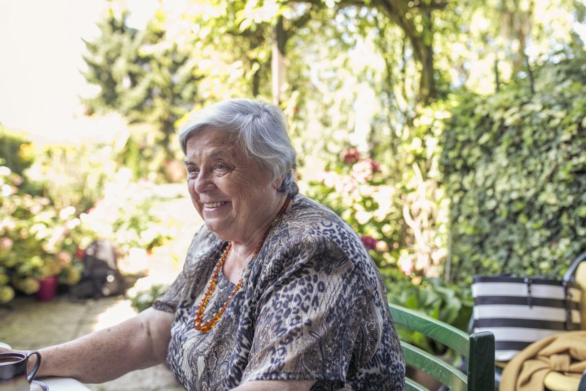 Eine alte Dame mit roter Perlenkette sitzt an ihrem Gartentisch und lächelt.