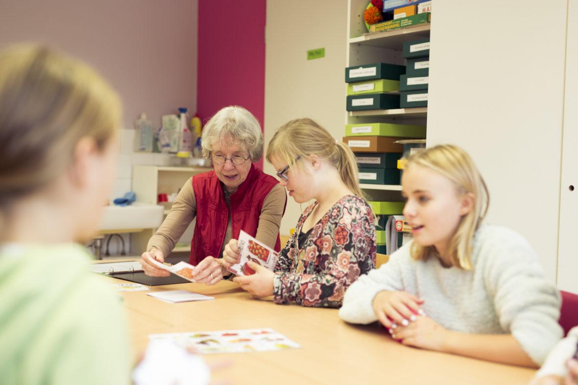 Eine ältere Frau gibt Kindern Spanischunterricht
