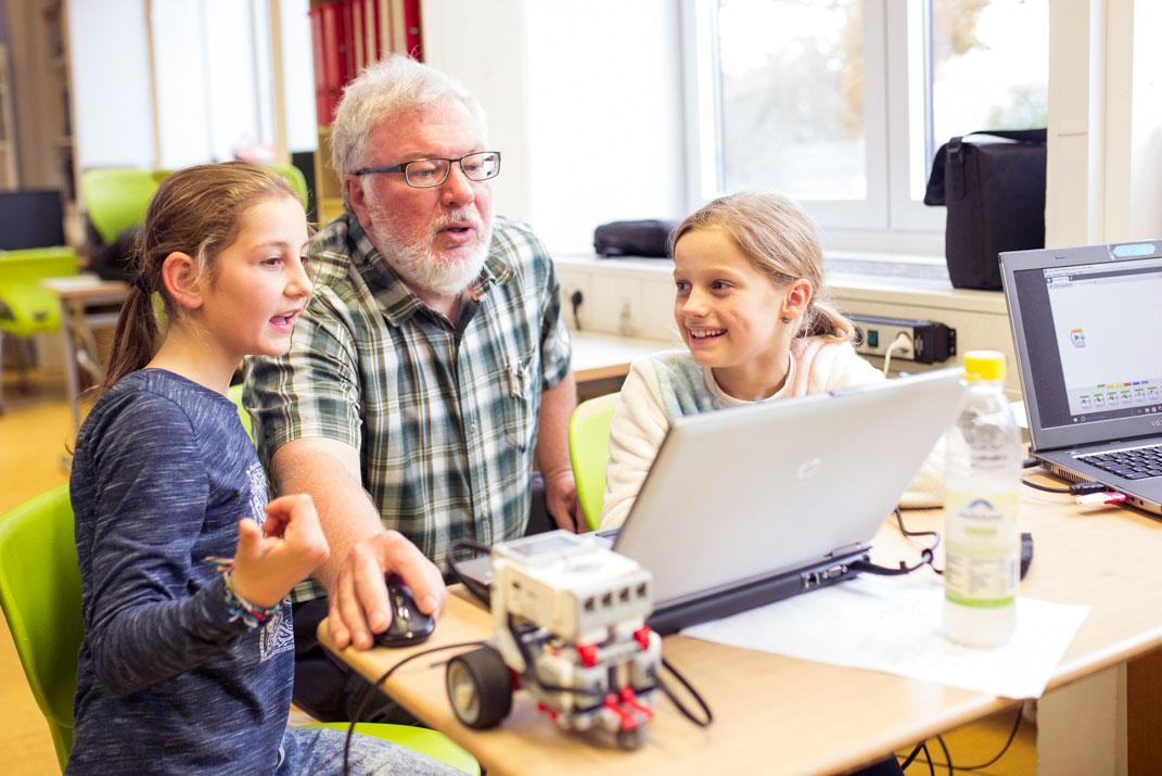 Kinder überarbeiten gemeinsam mit einem Senioren ihre Programmierung eines Roboters