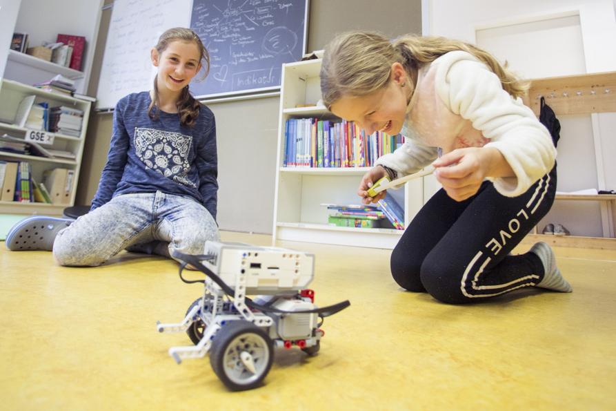 Mädchen spielen im Klassenraum mit ihrem Roboter.