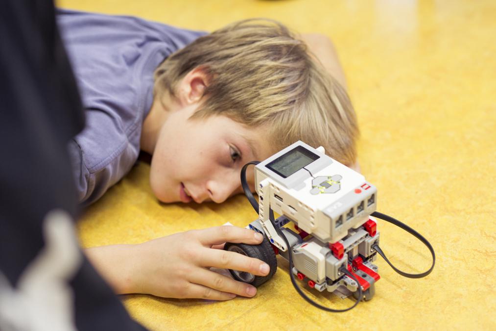 Ein Junge liegt am Boden und betrachtet seinen Roboter