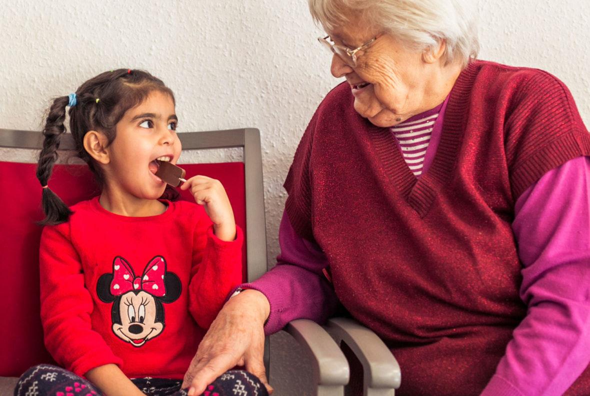 Eine Seniorin schaut erfreut zu, wie ein Mädchen einen Schokololli isst.