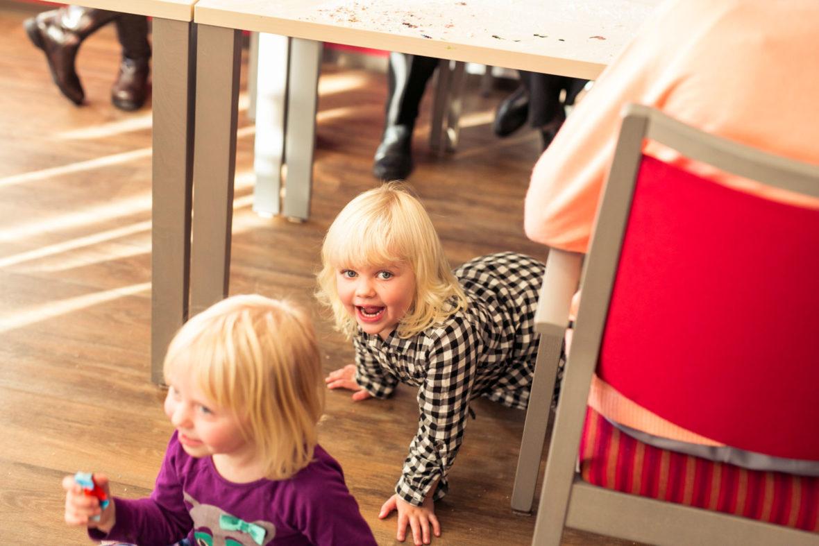 Zwei blonde, kleine Mädchen krabbeln unter einem Tisch hervor.