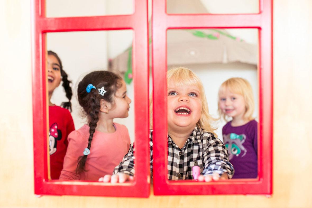 Vier Kinder stehen in einem Spielhäuschen und klappen die Fenster zu und lachen.
